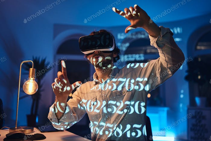 Astonished caucasian man with virtual reality glasses in office room