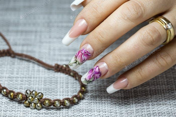 Blumen auf einem transparenten Lack auf den Nägeln