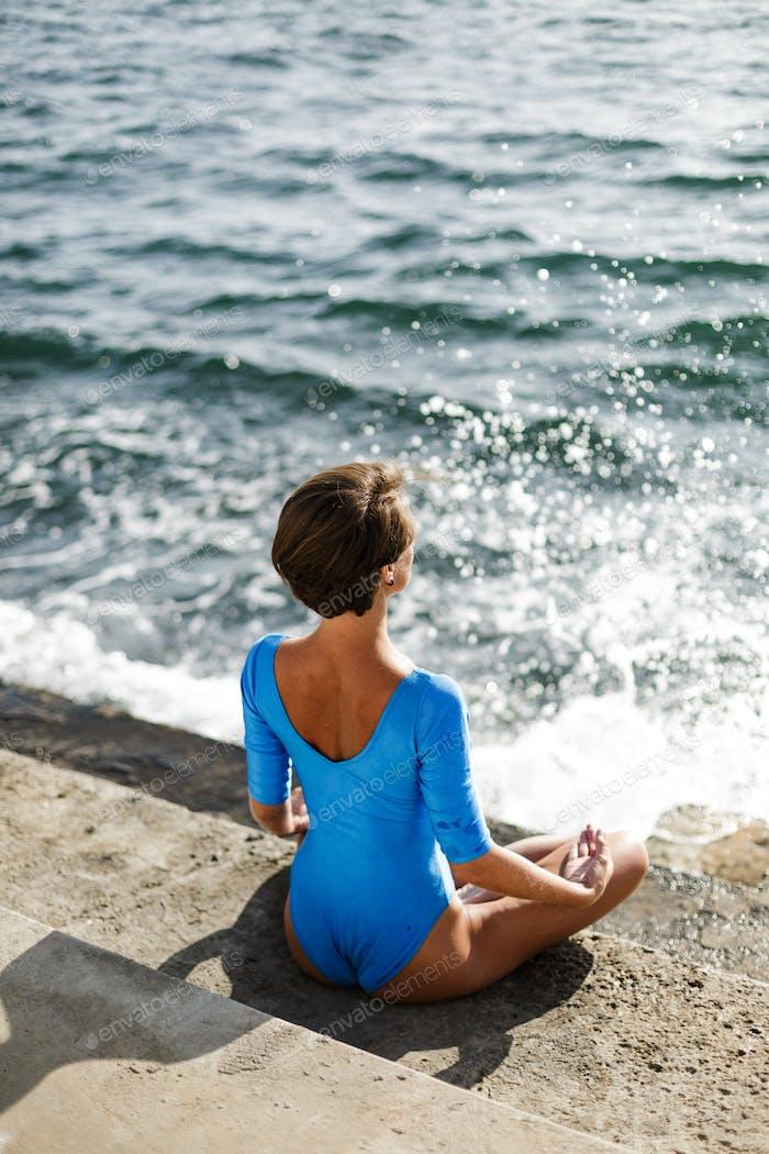 Schöne Dame in blauen Badeanzug üben Yoga mit erstaunlichem Meerblick auf dem Hintergrund