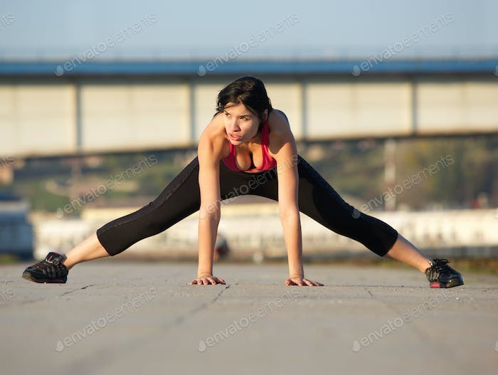 Fit young woman stretching muscles outdoors