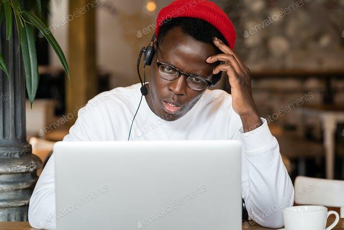 Hombre negro con auriculares viendo webinar educativo en el ordenador portátil, trabajo en línea en la cafetería. Aprendizaje electrónico.