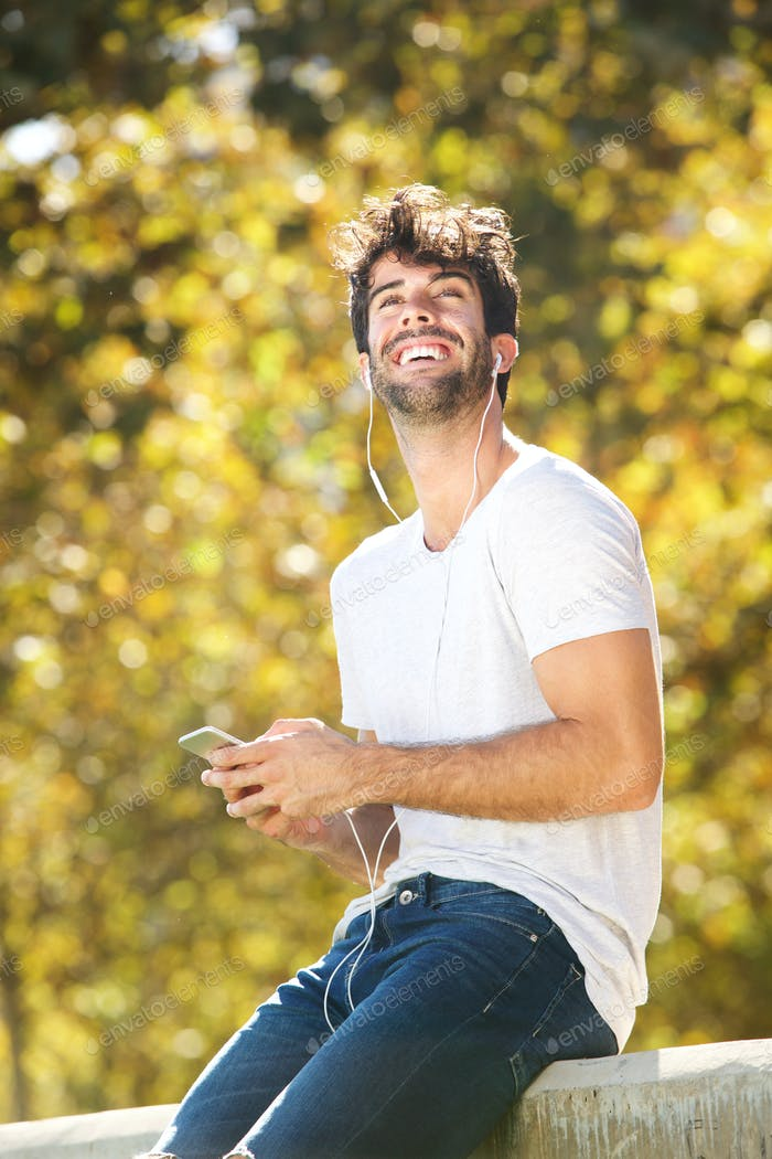 Happy man sitting on wall in park with cellphone
