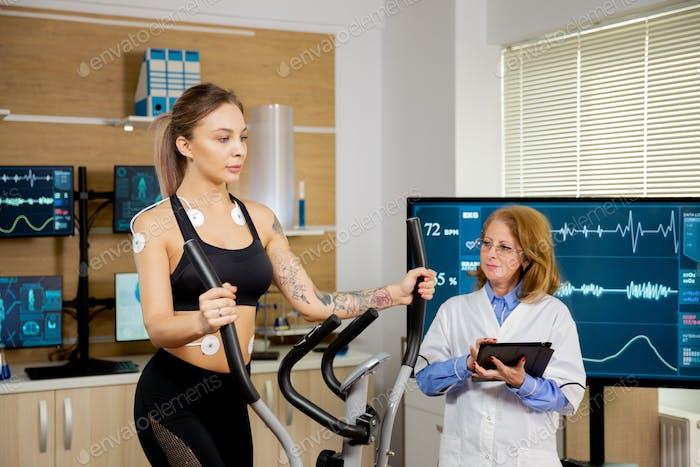 Спортсменка, которая проводит тесты на шагу и имеет электроды на ней, и врач следит за ней
