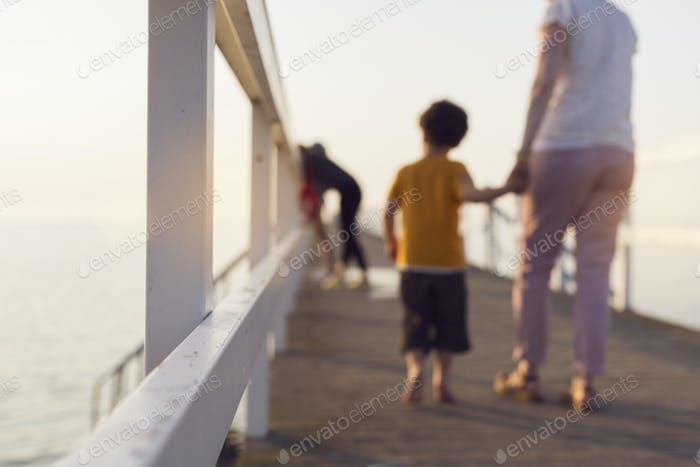 Mother and son (4-5) walking on pier, holding hands