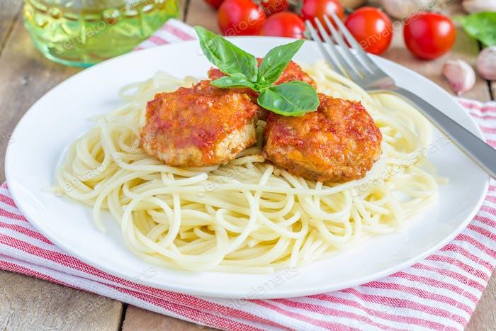 Fleischbällchen in Tomatensauce mit Spaghetti auf einem weißen Teller