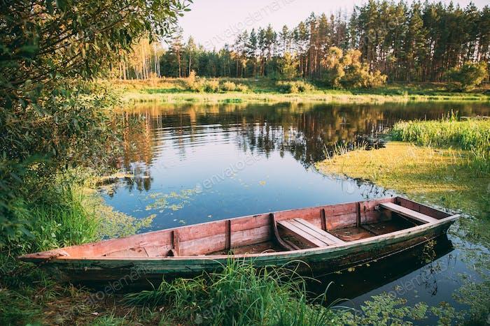 Old Wooden Rowing Fishing Boat Near Lake River Coast At Beautifu