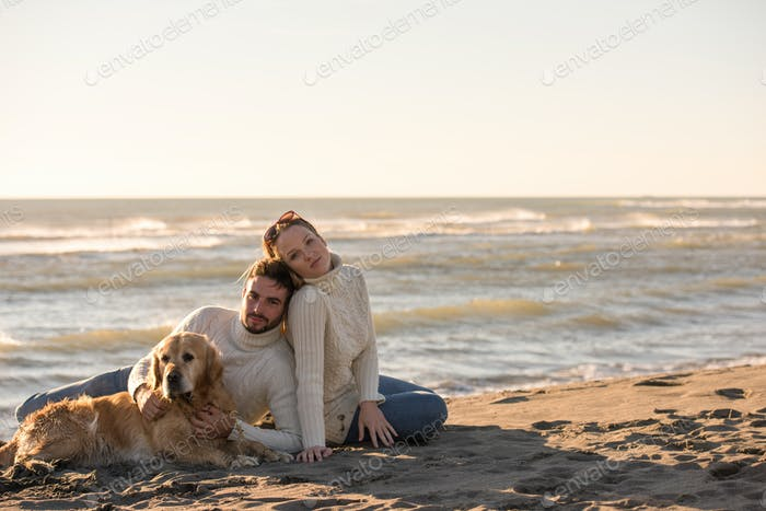 Couple with dog enjoying time on beach