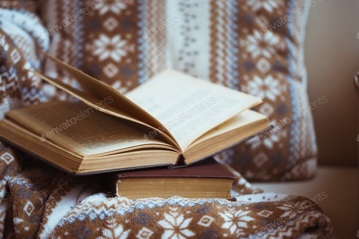 Stack of books with warm plaid on chair