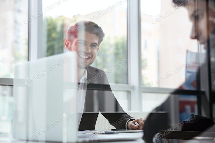 Zwei fröhliche junge Geschäftsleute mit Laptop auf Geschäftstreffen