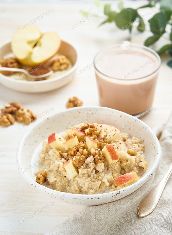Haferflocken mit Apfel, Nüssen, Honig und Tasse Schokolade auf weiß