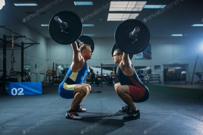 Two male weightlifters doing squats with barbells