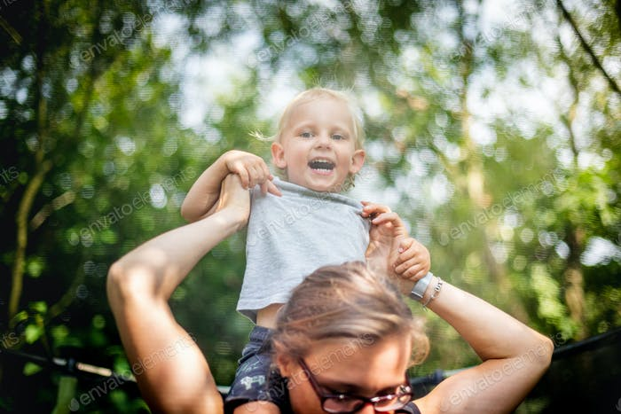 Little child enjoying a piggyback on his mothers back while playing outdoor in backyard