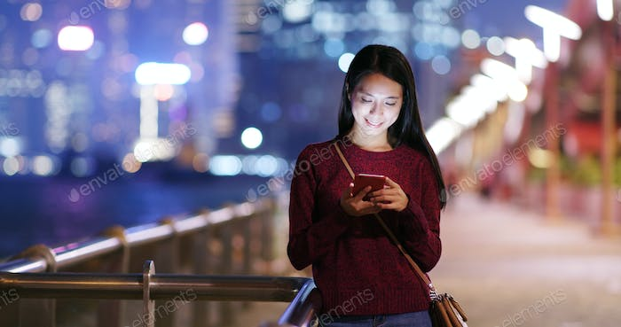 Woman check on mobile phone in city