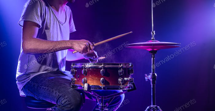 A drummer plays drums on a blue background. Beautiful special effects of light and smoke.