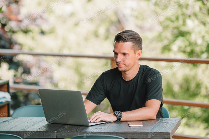 Young man with laptop works from home
