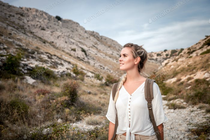 Beautiful tourist girl on hiking trail in mountain looking at landscape
