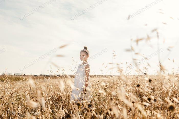 Little girl in golden field, sky background.