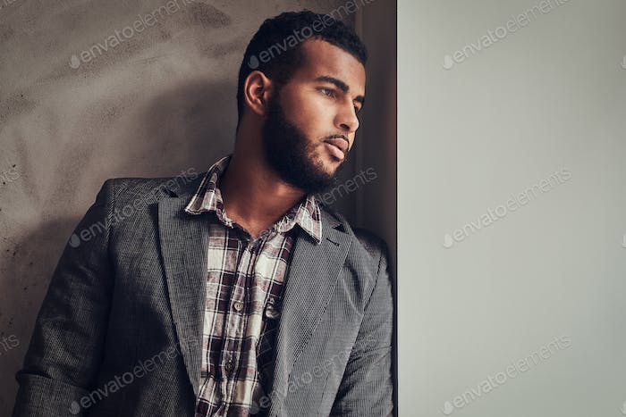 African-American guy leaning on a wall and looking away.