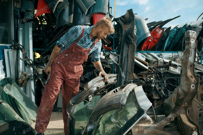 Male repairman choosing spare parts on car junkyard