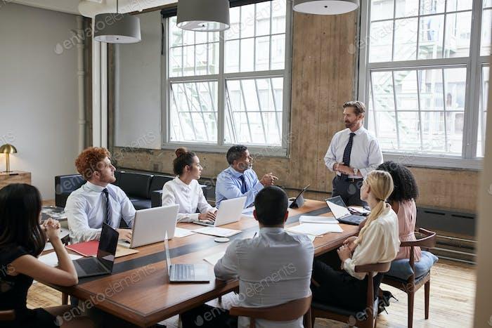 Бородатый бизнесмен обращается к коллегам на заседании совета директоров