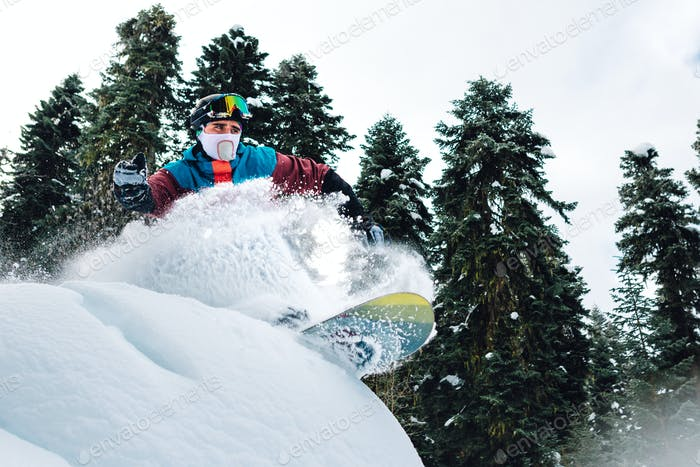 snowboarder is jumping, riding and freeriding the mountain forest