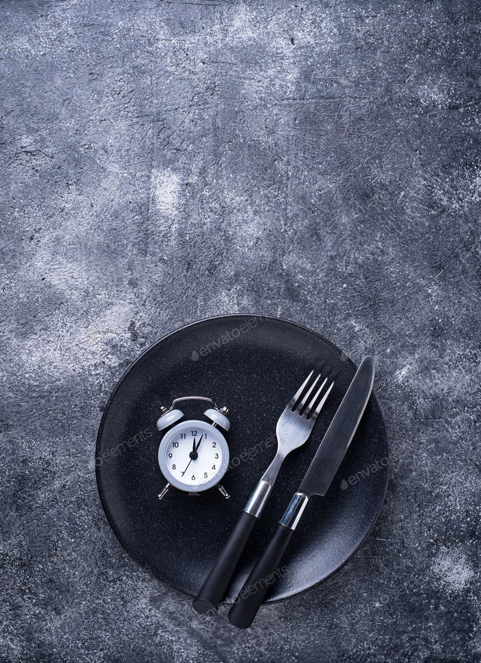 Grey alarm clock in empty plate.