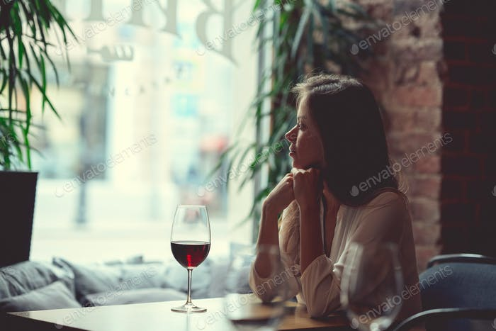 Young attractive girl with a glass of red wine