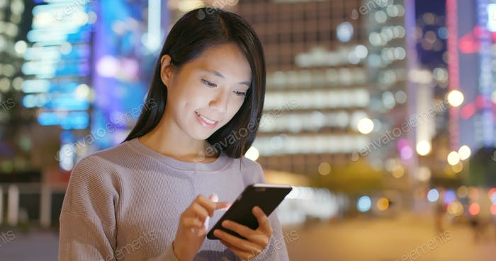 Frau Verwendung von Smartphone in der Stadt in der Nacht