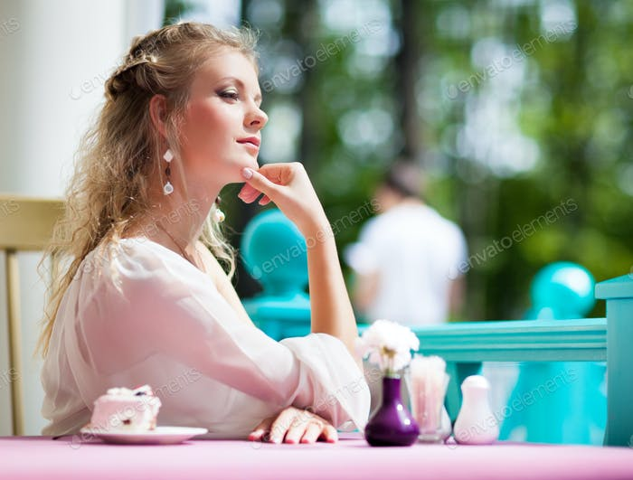 Beautiful young woman sitting at table