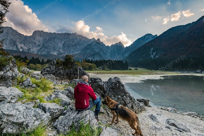 Adventure man with dog sitting at rock looking at alpine lake