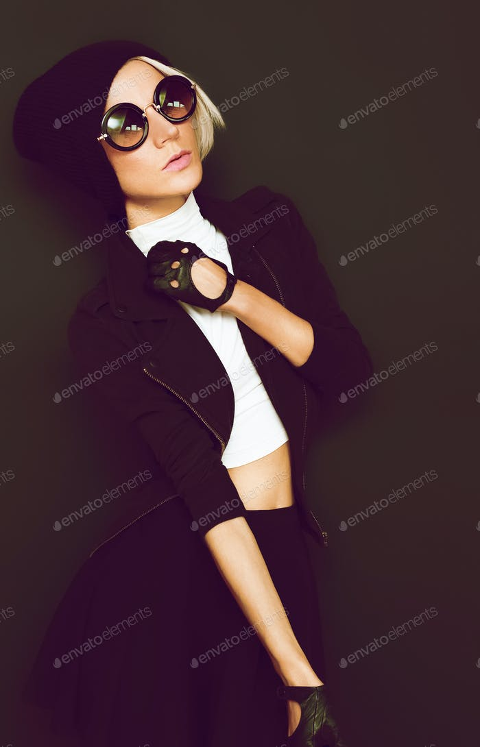 Glamorous blonde on a black background autumn fashion style