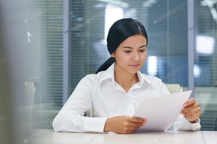 Pretty young businesswoman reading financial document