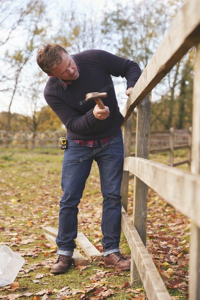 Reifen Mann hämmern Nagel in repariert Zaun