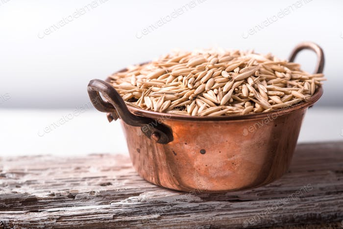 Oats in a copper bowl on a wooden stand side view