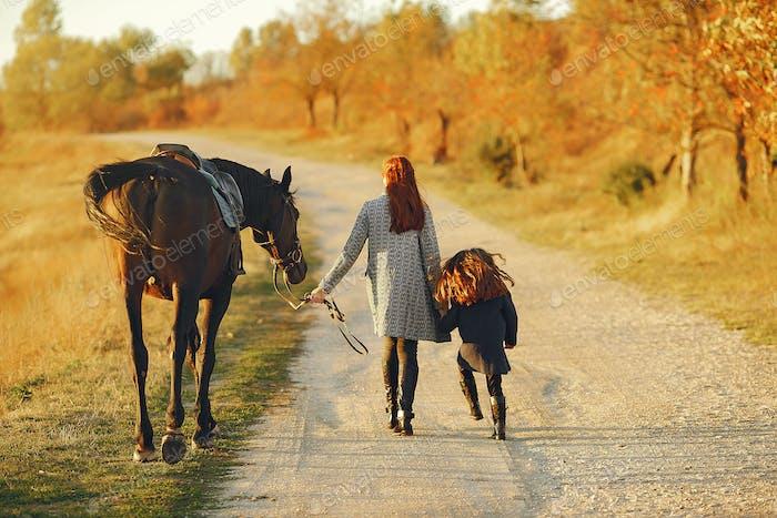 Mutter und Tochter auf einem Feld spielen mit einem Pferd