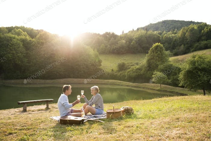 Senior couple at the lake having a picnic.