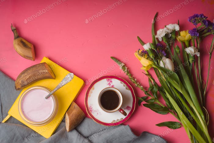 Bouquet of flowers, yogurt, cup of coffee on a pink table