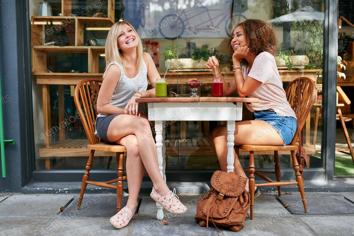 Female friends hanging out at sidewalk cafe