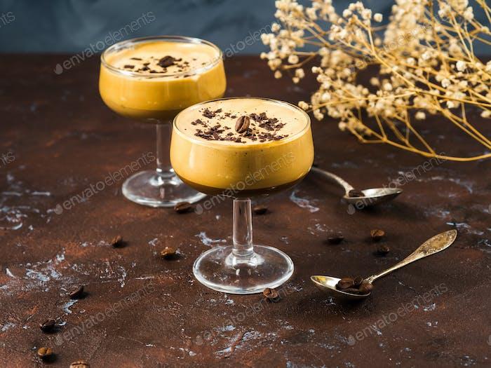 Frappe Kaffee in Dessertgläsern auf braunem Hintergrund