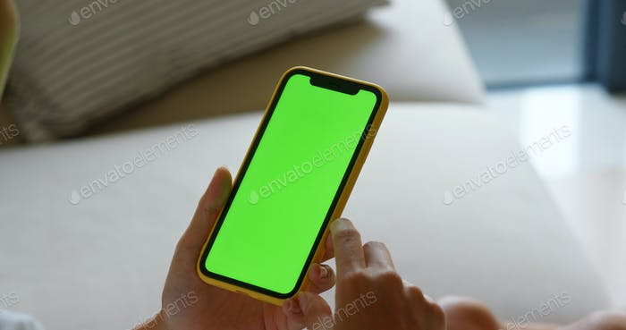 Woman use of cellphone with green screen at home