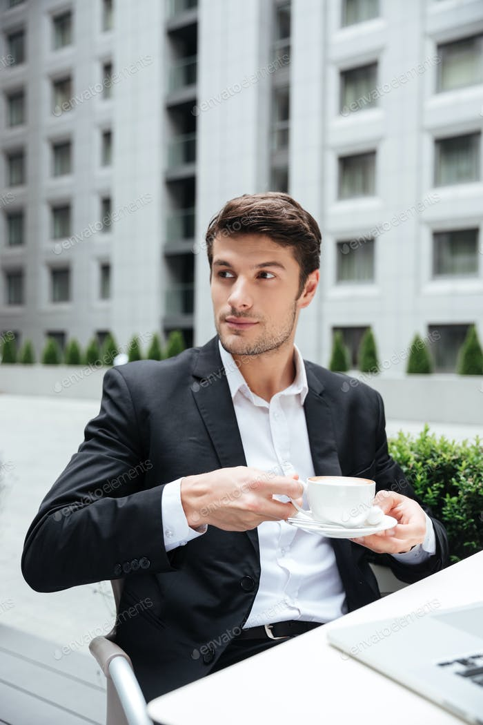 Businessman drinking coffee in outdoor cafe