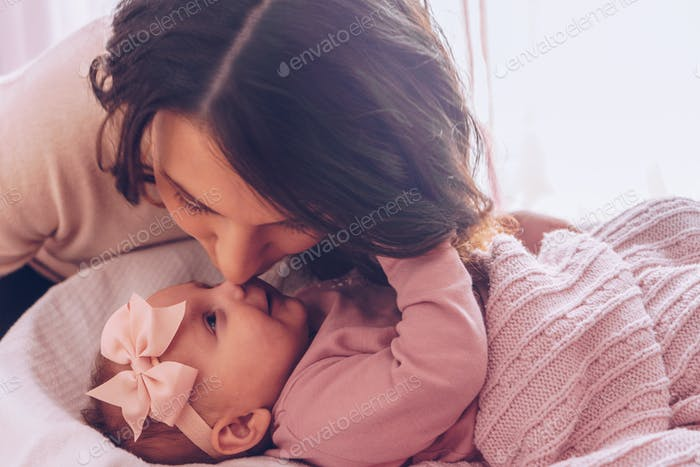 Young mother kissing her adorable baby girl.