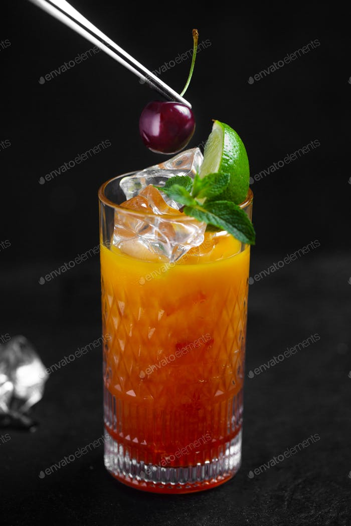 The chef decorates the drink with cherries with tweezers