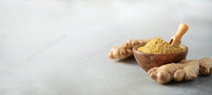 Ingwerwurzel und Ingwerpulver in Holzschüssel über grauem Betonuntergrund mit Kopierraum. Immunität