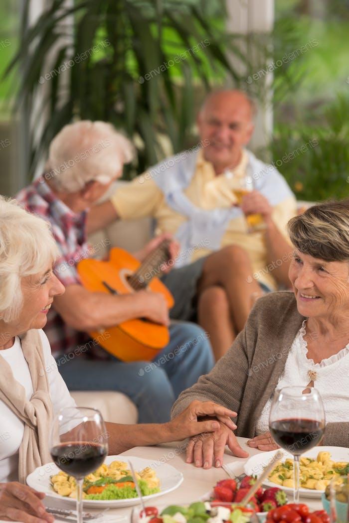 Two senior women drinking wine