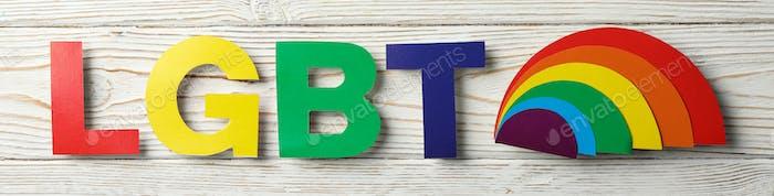 Letras de colores LGBT sobre fondo de madera blanco