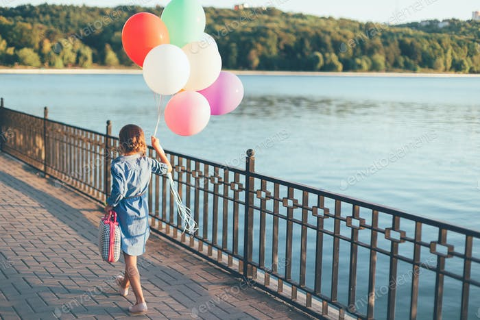 Walking girl holding colorful balloons and childish suitcase