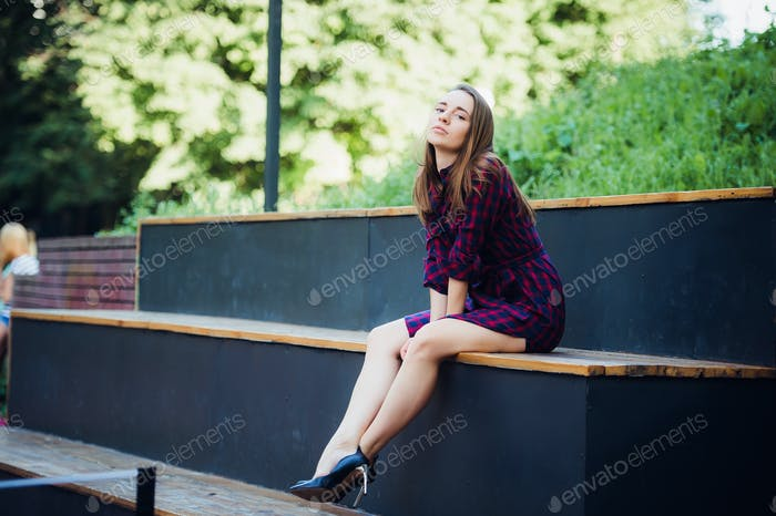 Girl wearing checkered dress sitting down in skatepark looking at camera.