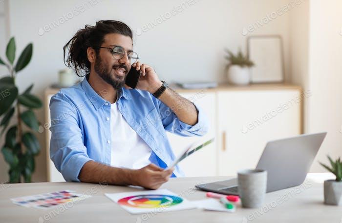 Western Man Freiberufler Designer im Gespräch mit dem Kunden auf dem Handy, diskutieren zukünftiges Projekt