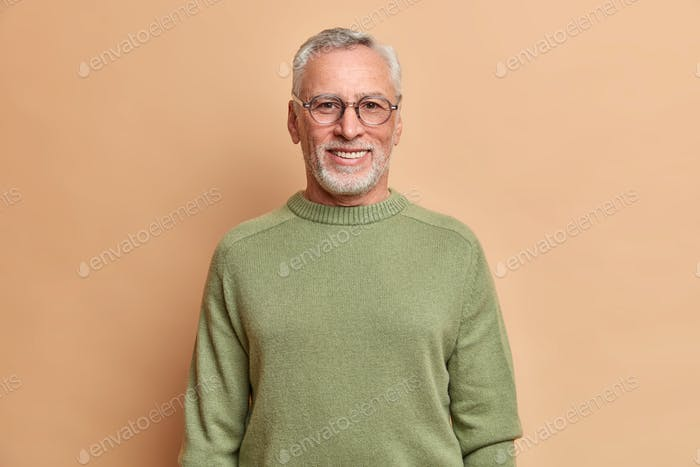 Half length shot of cheerful senior man smiles happily with white teeth wears optical glasses and sw